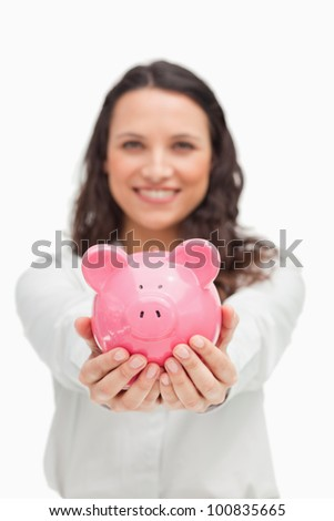 Brunette showing a piggy bank against white background