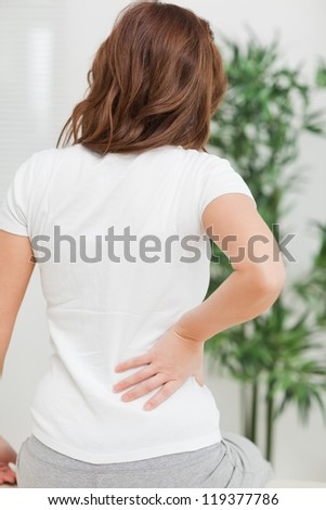 Brunette sitting while massaging her painful back in a room