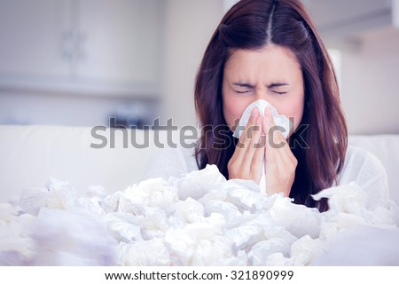 Brunette sneezing in a tissue against used tissues