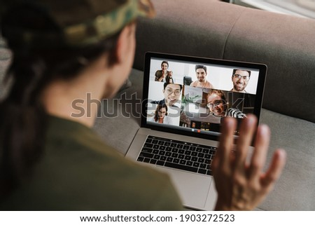 Brunette soldier woman waving hand while making conference call on laptop indoors