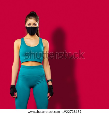 Brunette sportwoman wearing blue fitness clothing and black medical protective face mask training indoors. Fitness fit form, health and body care during covid-19 on red background. High quality photo Foto stock ©