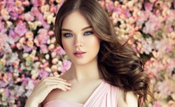 Brunette spring girl with long  and   shiny wavy hair .  Beautiful  model woman with curly hairstyle ,   background  wall of flowers . Skin Care, beauty and  spa