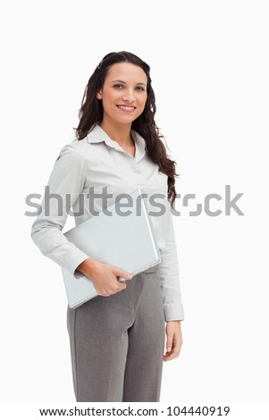 Brunette standing while holding a laptop against white background