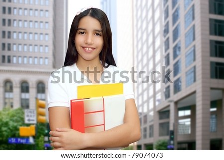 Brunette student young girl teen latin holding books modern city buildings [Photo Illustration]