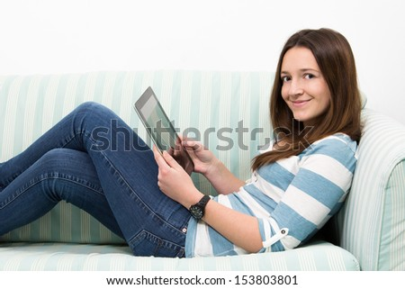 Brunette Teenage Girl Working On A Table PC whole lying on a couch