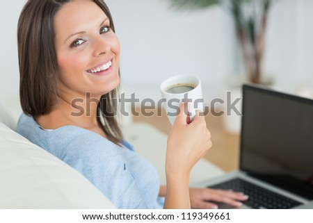 Brunette using her laptop and drinking a cup of coffee in the living room