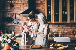 Brunette with holds baby and senior lady looking to the granddaughter preparing dinner in kitchen.
