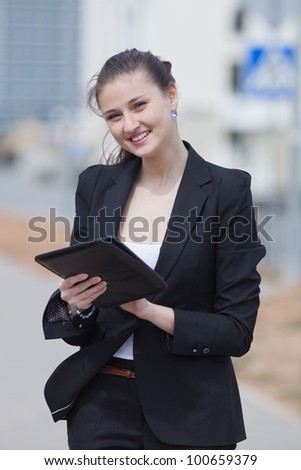Brunette with tablet on open air. Young woman in black suit with tablet computer in her hands looking at camera smiling
