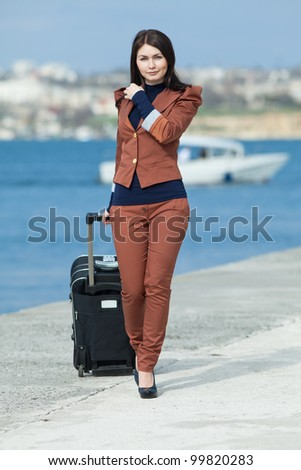 Brunette with valise on seashore. Young woman in brown suit with rolling suitcase walking along the seafront - stock photo