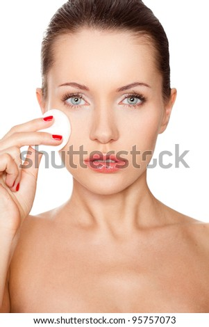 brunette woman cleaning her face with cotton sponge