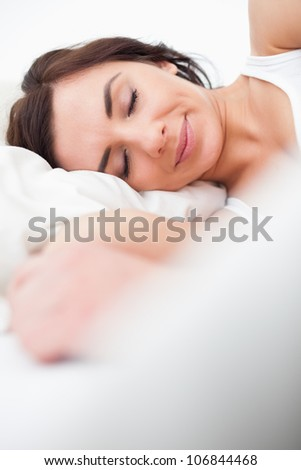 Brunette woman closing her eyes while lying in her bedroom