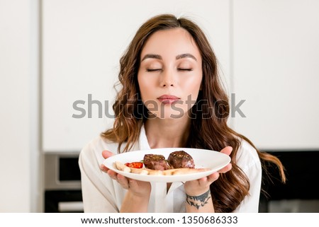 Brunette woman cooking and eating red meat steak with glass of red wine. Housewife concept