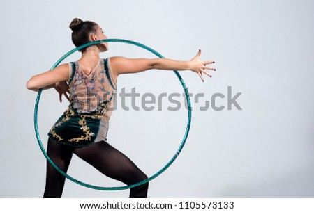 brunette woman doing exercise with a hula-hoop. Fitness woman. #1105573133