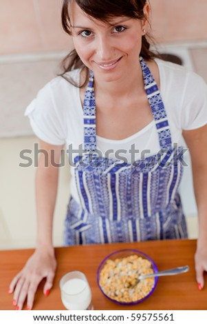 Brunette woman eating cereals in the kitchen
