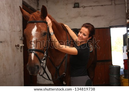 Brunette woman fastening the martingale on brown horse