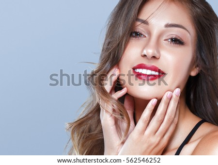 Brunette Woman girl with long and shiny wavy hair . Beautiful model with curly hairstyle and red lipstick lips.