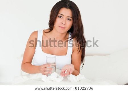 brunette woman having a cold sitting in bed taking pills looking into camera in bedroom
