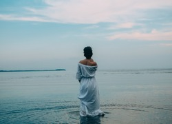 brunette woman in blue dress goes into the water sea color merges with the sky