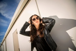Brunette woman in leather jacket and sunglasses casting a shadow while modeling in an industiral setting against white wall