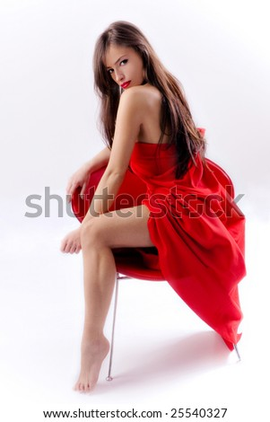 brunette woman in red dress sitting on a red chair - stock photo