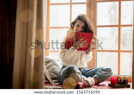 brunette woman in warm sweater and socks reading book sitting on windowsill in room decorated for celebrating new year and christmas looking happy festive mood