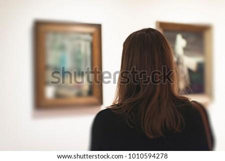 Brunette woman looking at artwork in museum. Rear view.