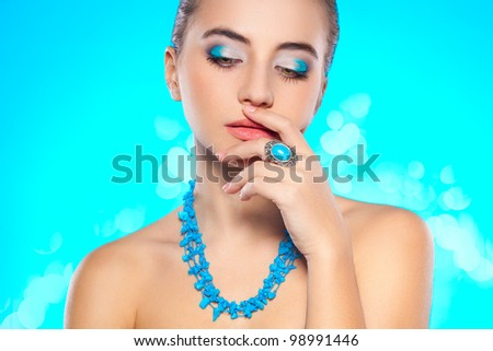 brunette woman looking down with turquoise necklace and ring on finger