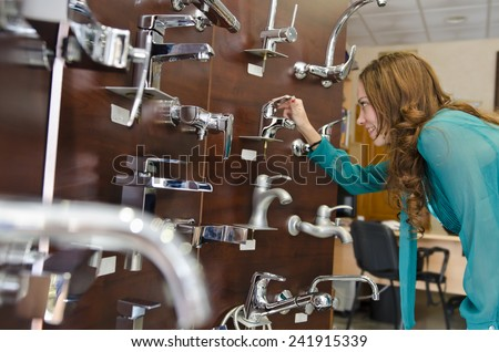 brunette woman looking faucets at plumbing store
