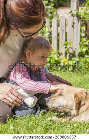 brunette woman mother and blonde baby two years old age touching with hand and petting a brown terrier breed dog belly lying over green grass lawn