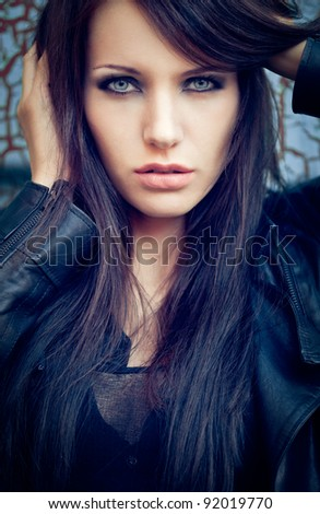 brunette woman near cracked wall. Specially toned fashion photo