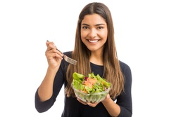 Brunette woman promotes wellness by eating salad on white background