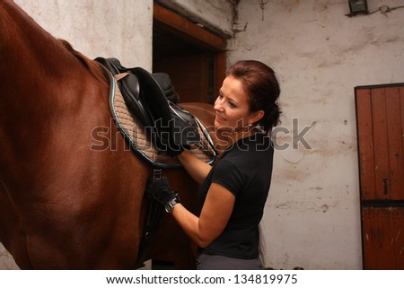Brunette woman saddling up brown horse in the stables