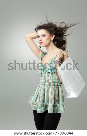 brunette woman shopping white bag wind hair