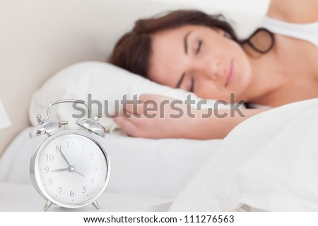 Brunette woman sleeping in the morning in her bedroom