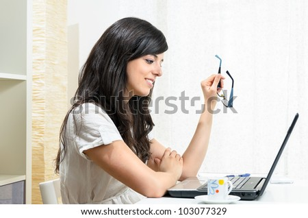 Brunette woman smiles while she looks her laptop screen and hold her glasses.