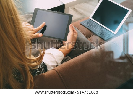brunette woman using digital tablet and laptop computer on sofa in living room #614731088