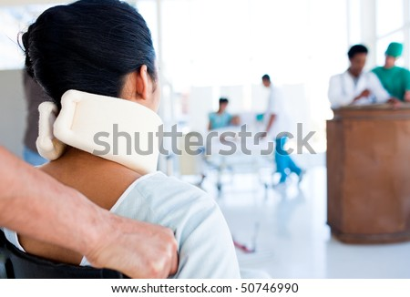 Brunette woman with a neck brace sitting on wheelchair in hospital