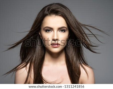 Brunette woman with beauty long brown hair. Fashion model with long straight hair. Fashion model posing at studio.Pretty woman with long straight brown hair looking at camera.