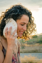 Brunette woman with curls listening to the sound of a conch shell