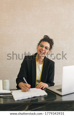 brunette woman with curly, upturned hair, round glasses and a white T-shirt with a black jacket, smiling and writing on a piece of paper with a grey pen and a laptop next to her, looking at the camera