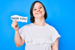 Brunette woman with down syndrome holding thank you paper looking positive and happy standing and smiling with a confident smile showing teeth