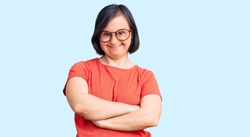 Brunette woman with down syndrome wearing casual clothes and glasses happy face smiling with crossed arms looking at the camera. positive person.