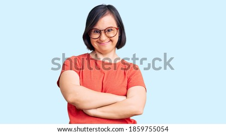 Brunette woman with down syndrome wearing casual clothes and glasses happy face smiling with crossed arms looking at the camera. positive person.  Сток-фото ©