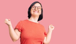 Brunette woman with down syndrome wearing casual clothes and glasses very happy and excited doing winner gesture with arms raised, smiling and screaming for success. celebration concept.