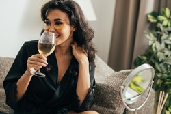 Brunette woman with eye patches drinking wine. Young female in satin robe relaxing at home on couch.