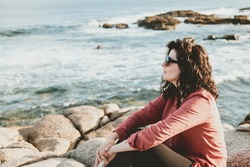Brunette woman with glasses contemplating the sea from the rocks