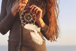 Brunette woman with long hair holding dream catcher in her hands