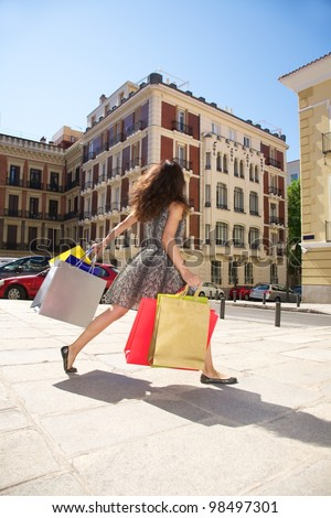 brunette woman with shopping bags walking in Madrid city Spain