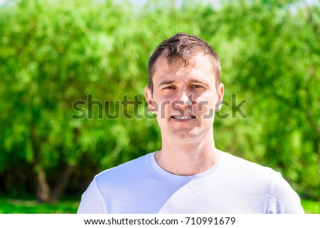 Brunette 35 years old in a white T-shirt on the background of a green summer park