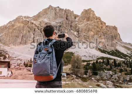 Brunette young man with big backpack spending time outdoor under gray sky enjoying rocky landscape. Guy in black shirt taking photo of mountains during travel around Italy.